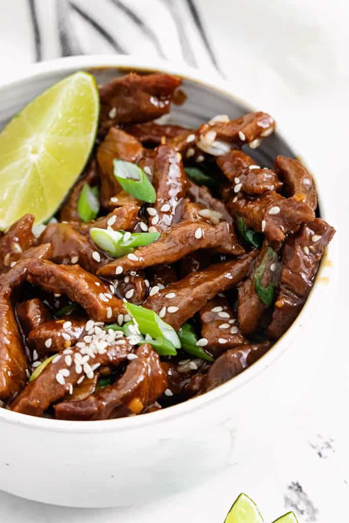 sesame beef with a lime wedge in white bowl