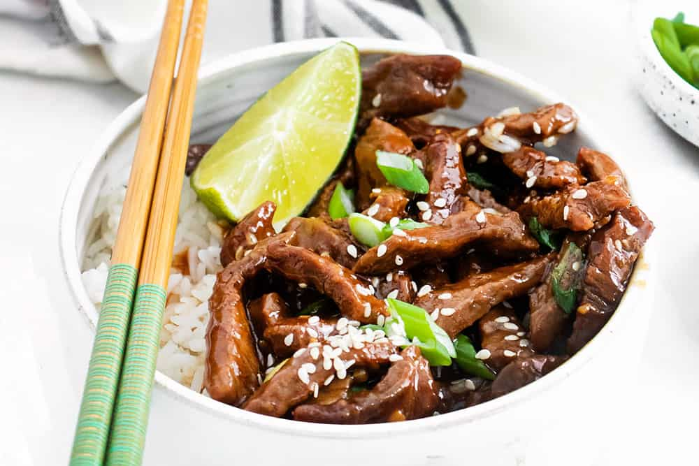 bowl of sesame beef with white rice topped with chopsticks
