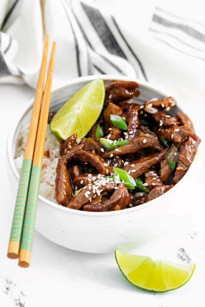chopsticks resting on white bowl with sesame ginger beef and rice