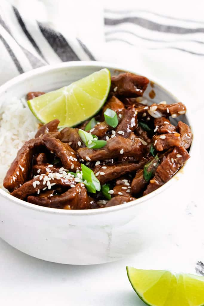 bowl of sesame ginger beef with lime wedge