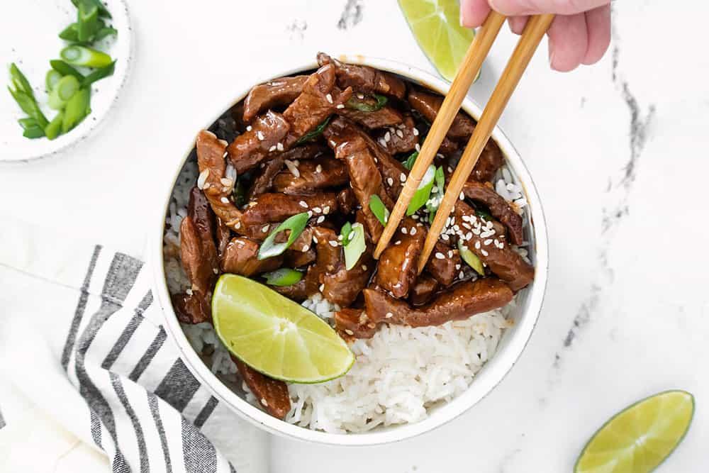 chopsticks picking up piece of sesame ginger beef in bowl