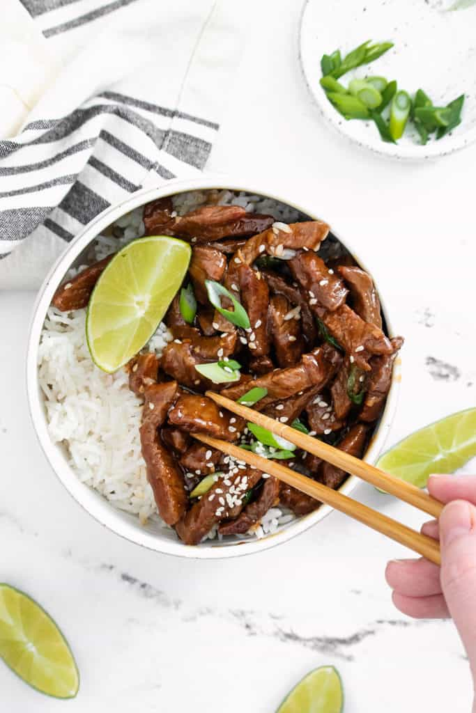 chopsticks eating bowl of sesame ginger beef and rice