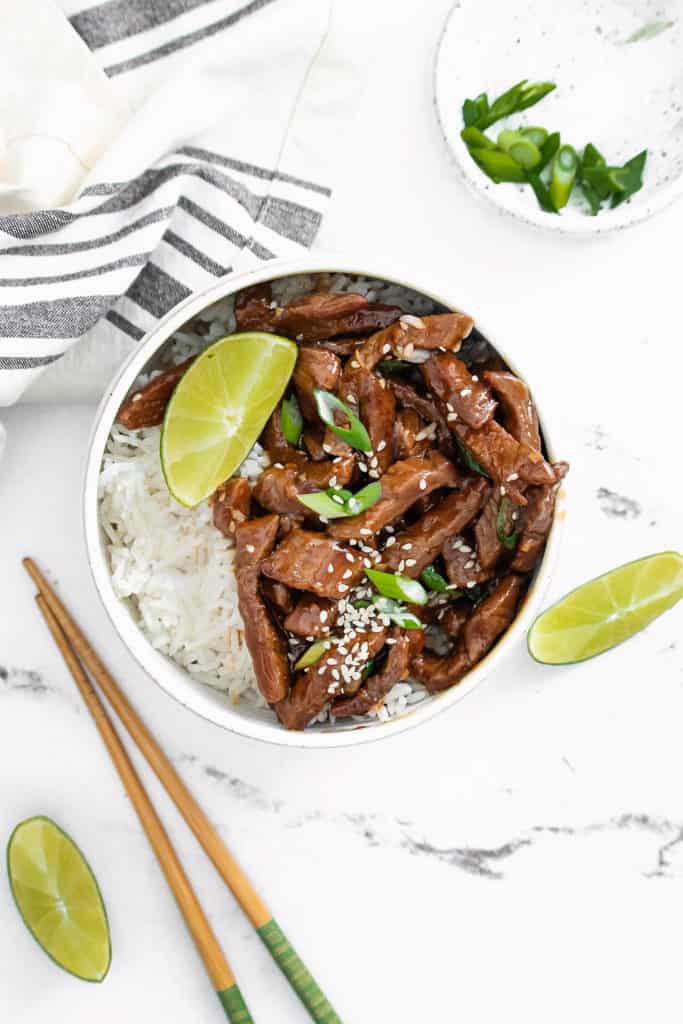 bowl of sesame ginger beef with rice in bowl on table