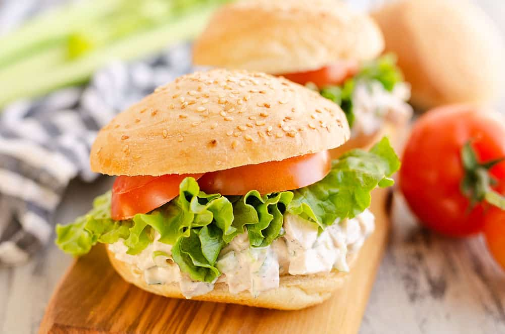 chicken salad sandwich on table with tomato and celery
