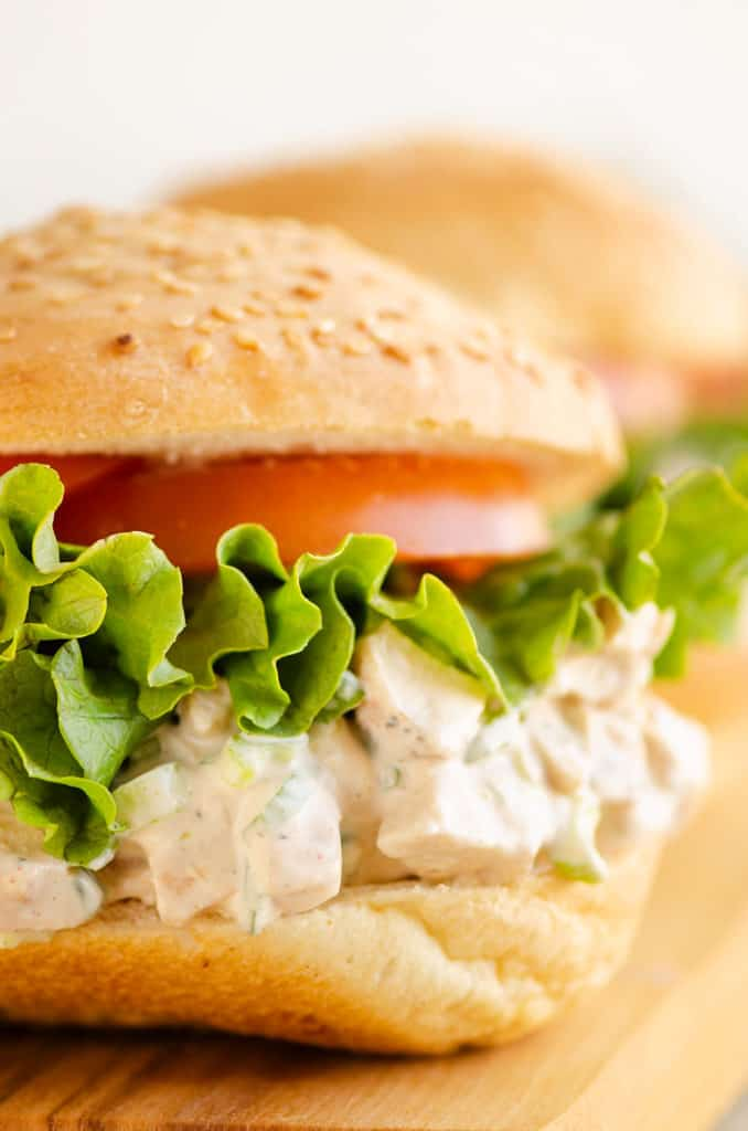sesame bun with smoked chicken salad, lettuce and tomato slice
