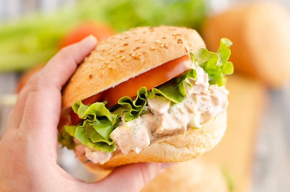 hand holding smoked chicken salad sandwich with lettuce and tomato