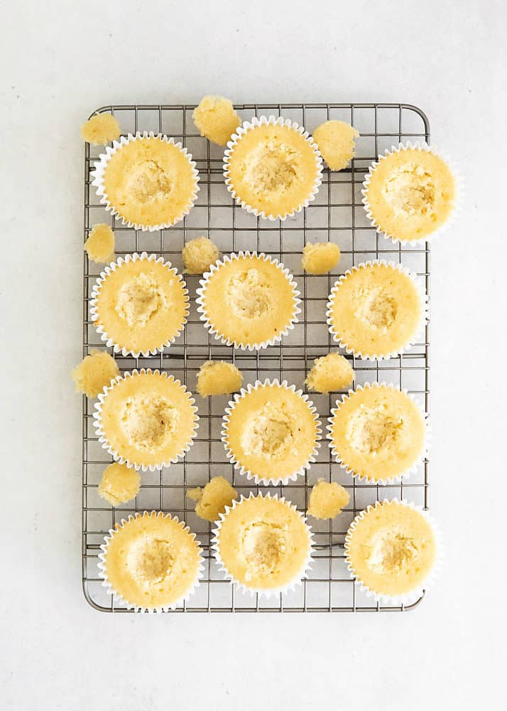 vanilla cupcakes wtih centers removed on cooling rack
