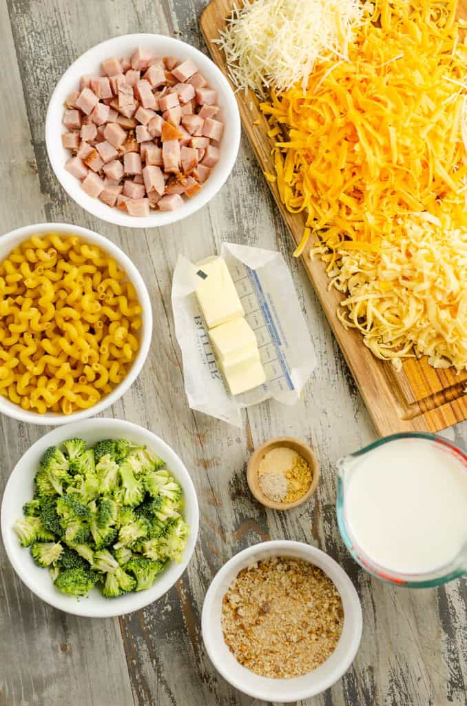 shredded cheese, diced ham, cavatappi pasta noodles, broccoli florets, breadcrumbs, butter, milk and spices on table