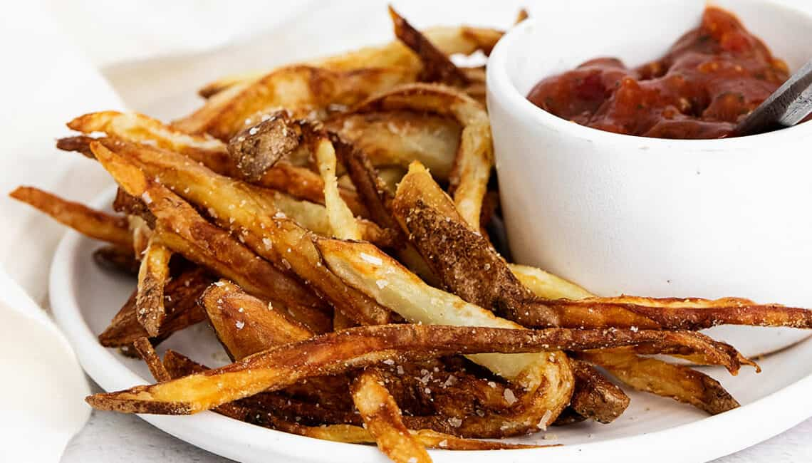 homemade french fries on plate with ketchup