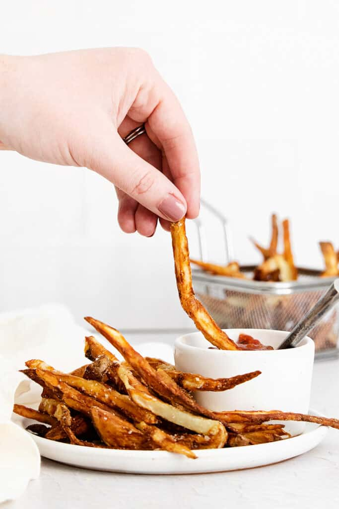french fries dipped in bowl of ketchup