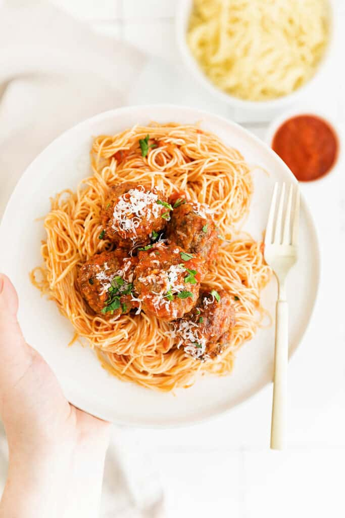 hand hplding plate filled with pasta and air fryer meatballs