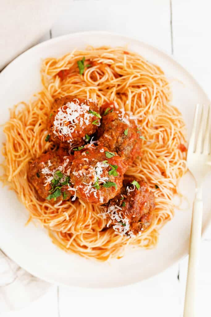 meatballs over pasta topped with grated parmesan cheese