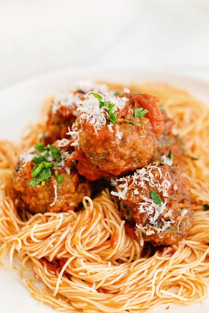 air fryer meatballs tossed in marinara over pasta and topped with parmesan and parsley