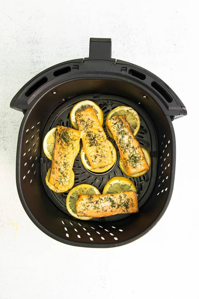 salmon cooked over lemon in air fryer basket