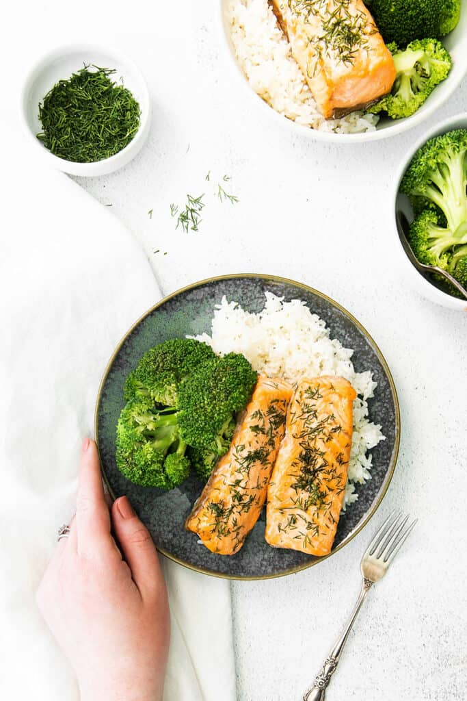 hand holding plate full of salmon rice and broccoli