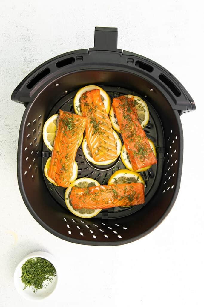 air fryer basket with salmon fillets over lemon slices