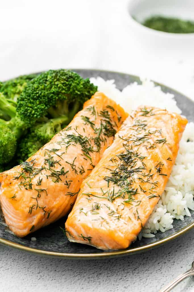 air fryer salmon fillets on plate with rice and broccoli