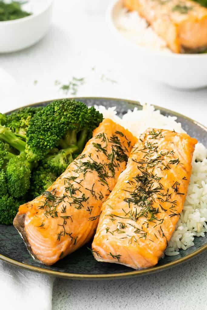 two lemon dill salmon fillets on dark plate