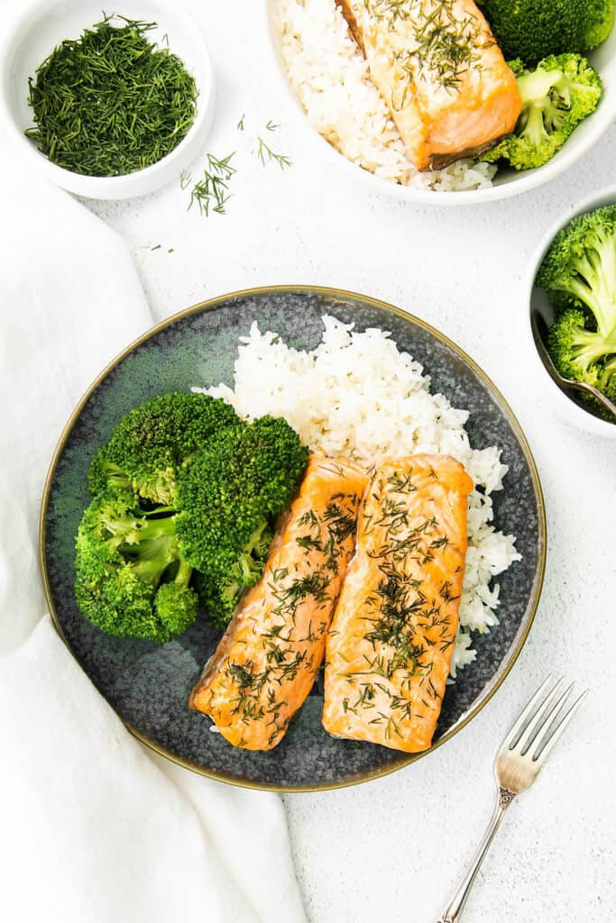 lemon dill salmon fillets on plate with rice and broccoli