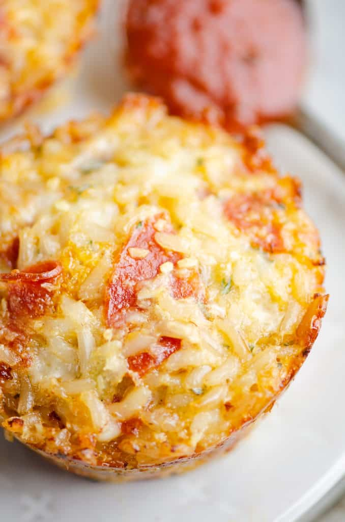 pizza rice muffin on plate with spoonful of pizza sauce