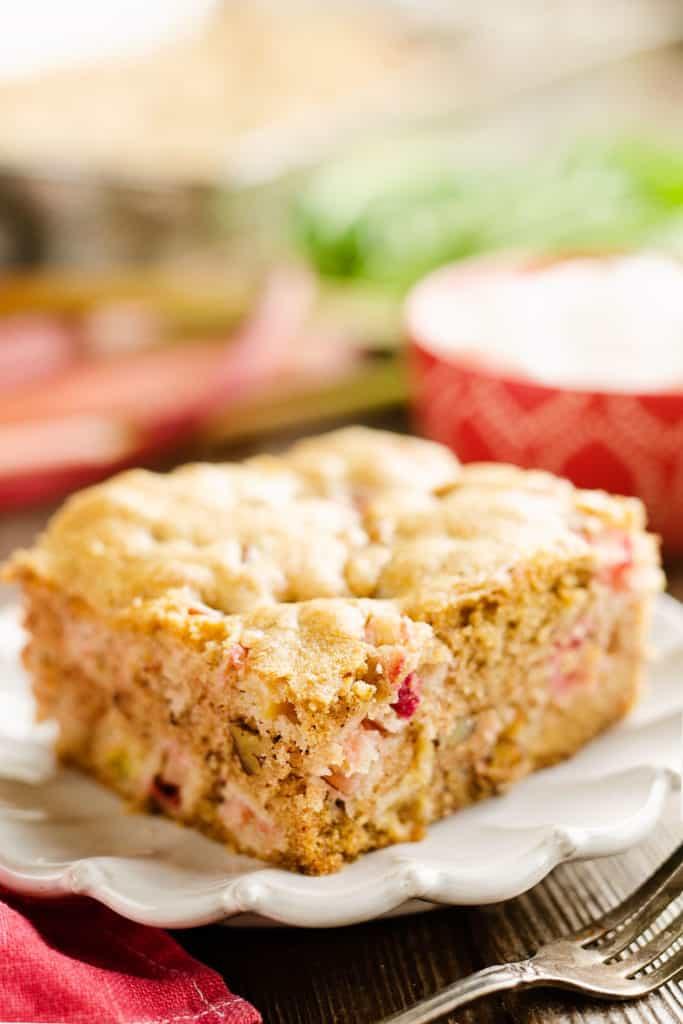 slice of rhubarb cinnamon cake on white plate with fork