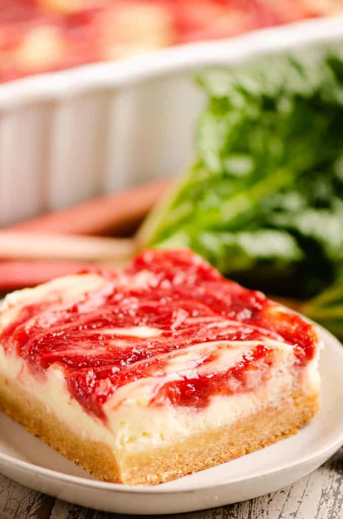 strawberry rhubarb cheesecake bar on white plate with stalks of rhubarb