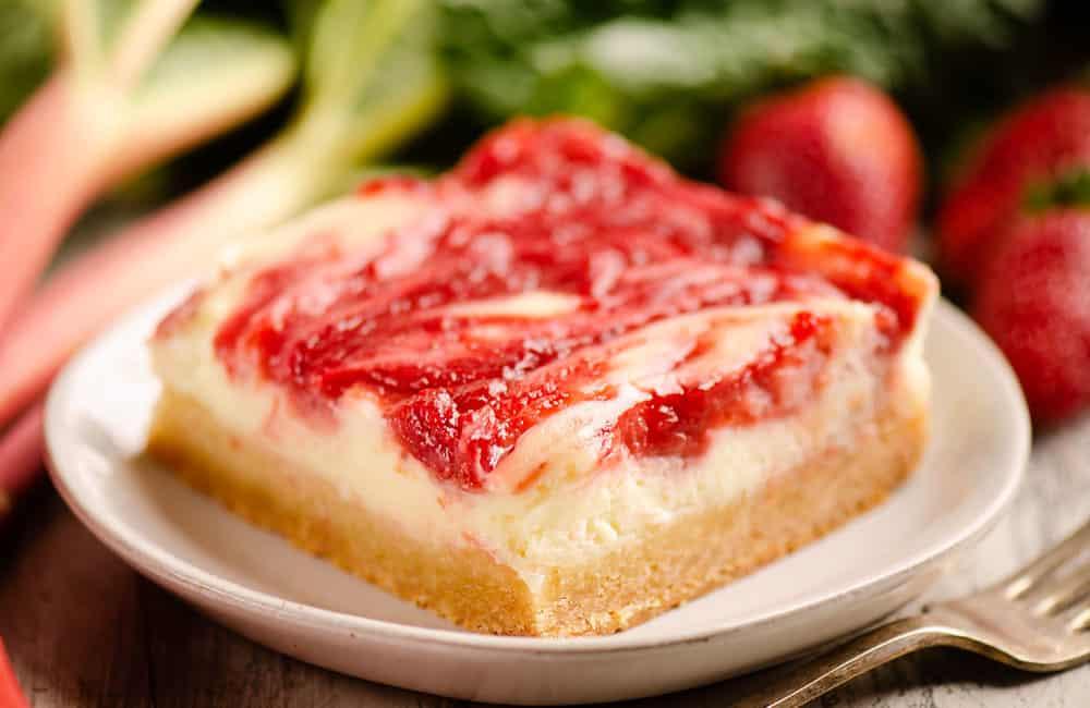 strawberry rhubarb cheesecake bar with sugar cookie crust on plate