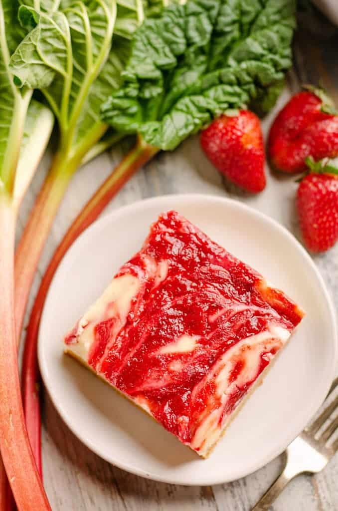 cheesecake swirl bar on plate with strawberries and rhubar