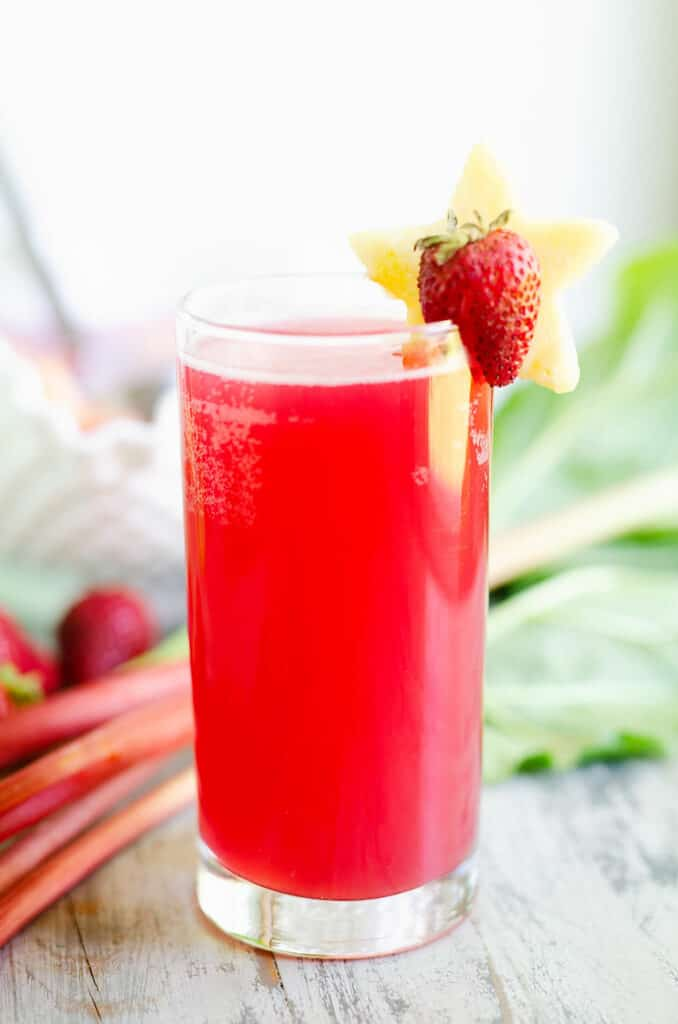 strawberry rhubarb punch in glass topped with pineapple and strawberry