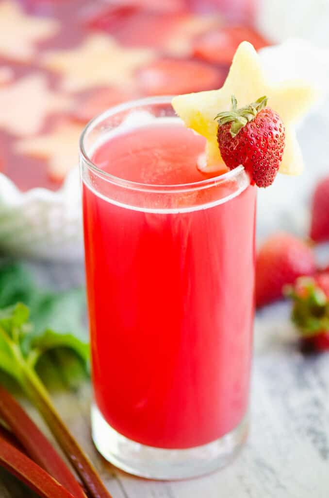 strawberry rhubarb punch in glass topped with pineapple star