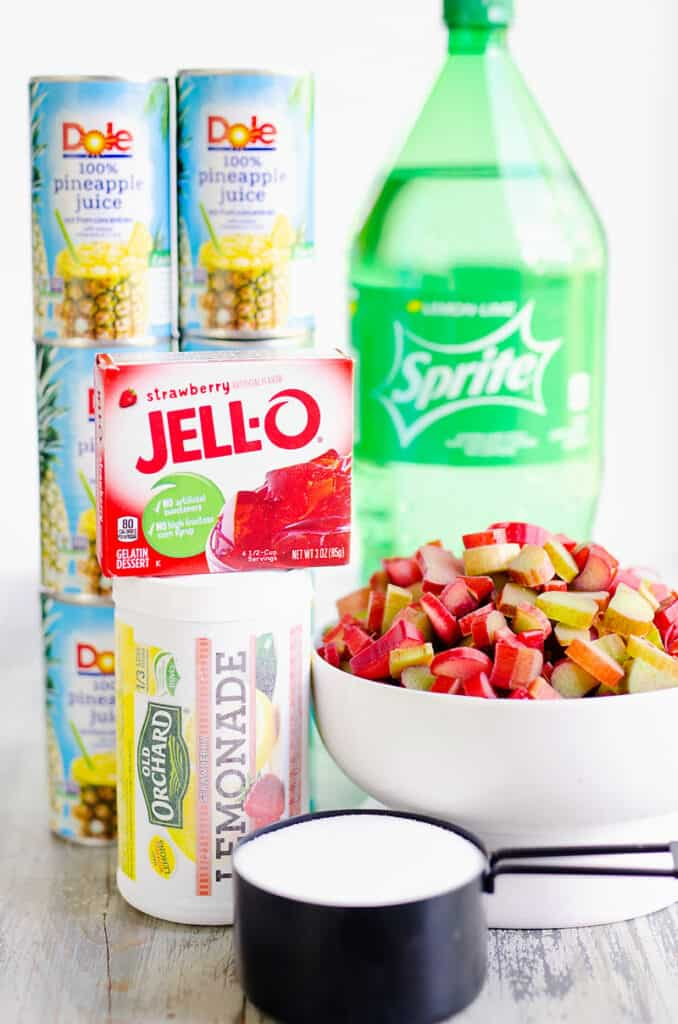 sprite, pineapple juice, strawberry jello, lemonade concentrate, chopped rhubarb and sugar on table
