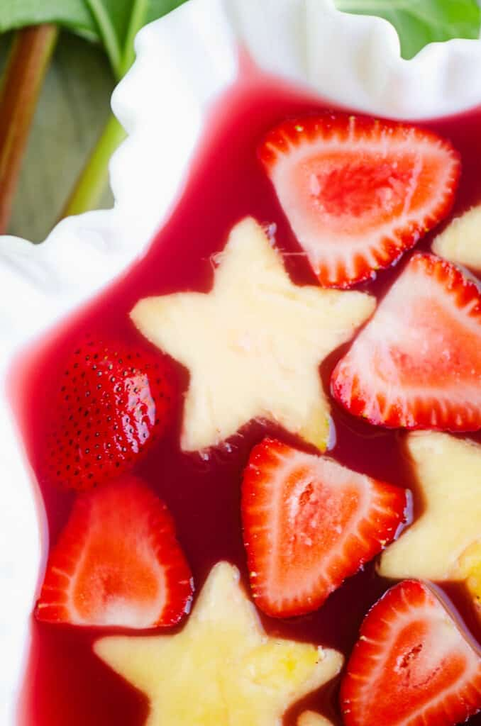 strawberry rhubarb punch in white bowl with fresh pineapple