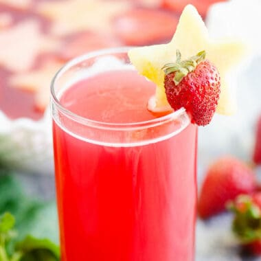 strawberry rhubarb punch in glass on table with strawberries