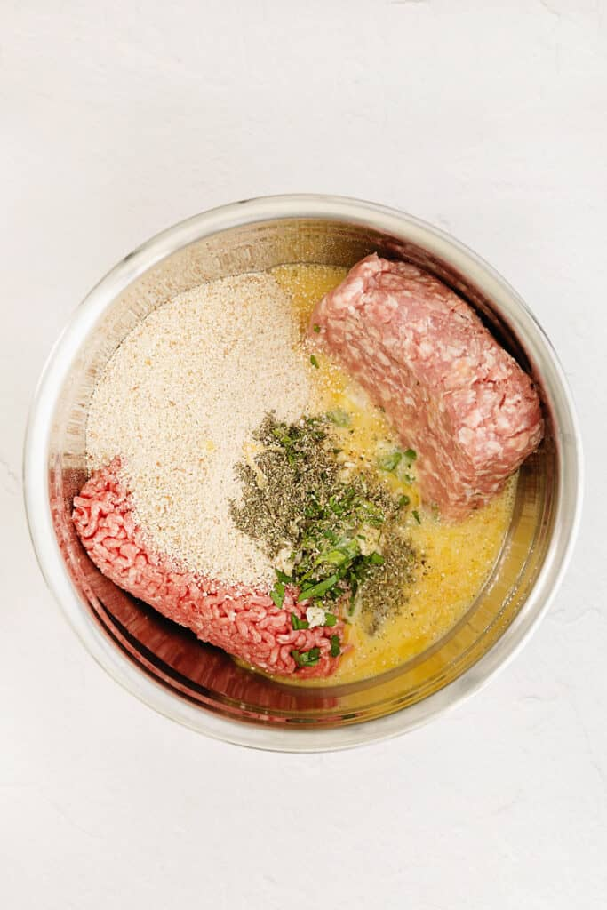 ground beef and pork with meatball ingredients in stainless steel bowl