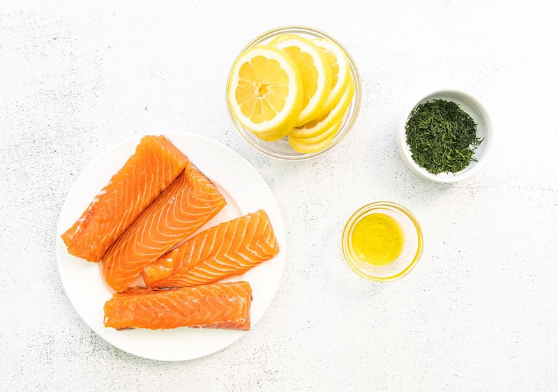 fresh salmon fillets, lemon slices, olive oil and dill on white table