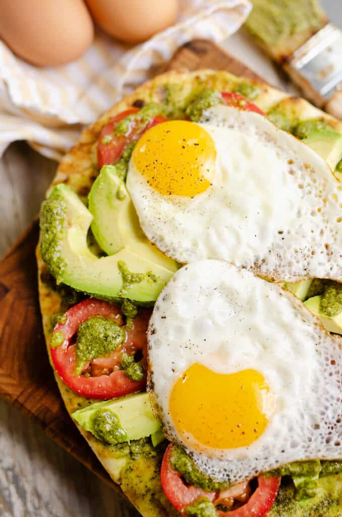 breakfast flatbread topped with sunny side up eggs