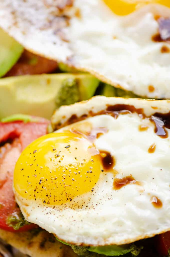 sunny side up egg drizzled with balsamic glaze over vegetables
