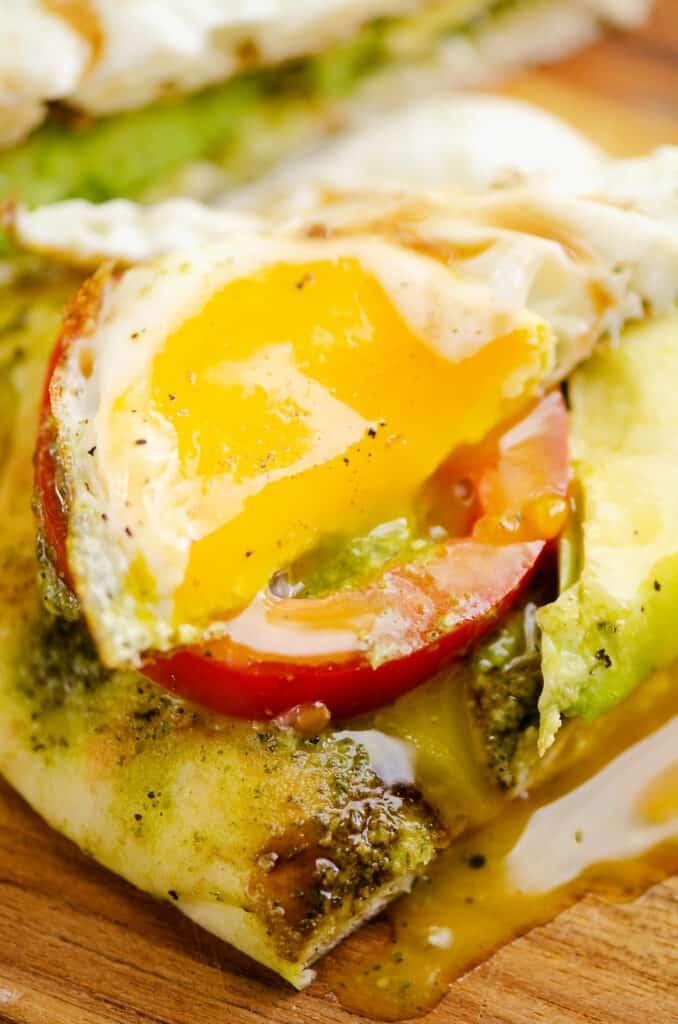 runny egg over tomato and avocado flatbread