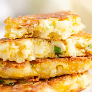 Corn fritter broken in half on stack of fritters