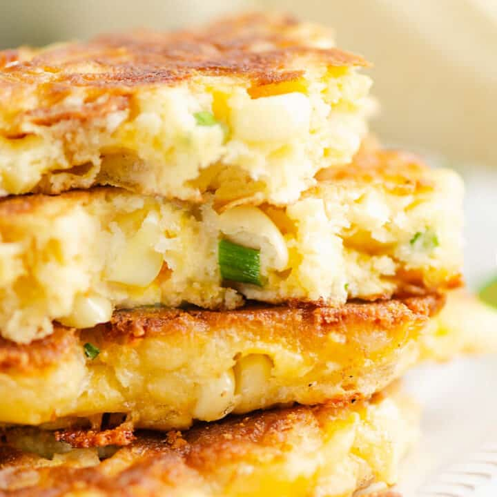 stack of corn fritters on plate with one broken in half