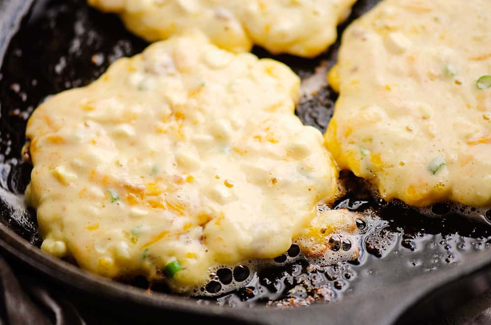 corn fritter sizzling in cast iron skillet