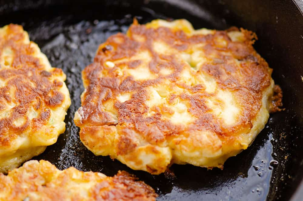 sweet corn fritter cooking in cast iron skillet