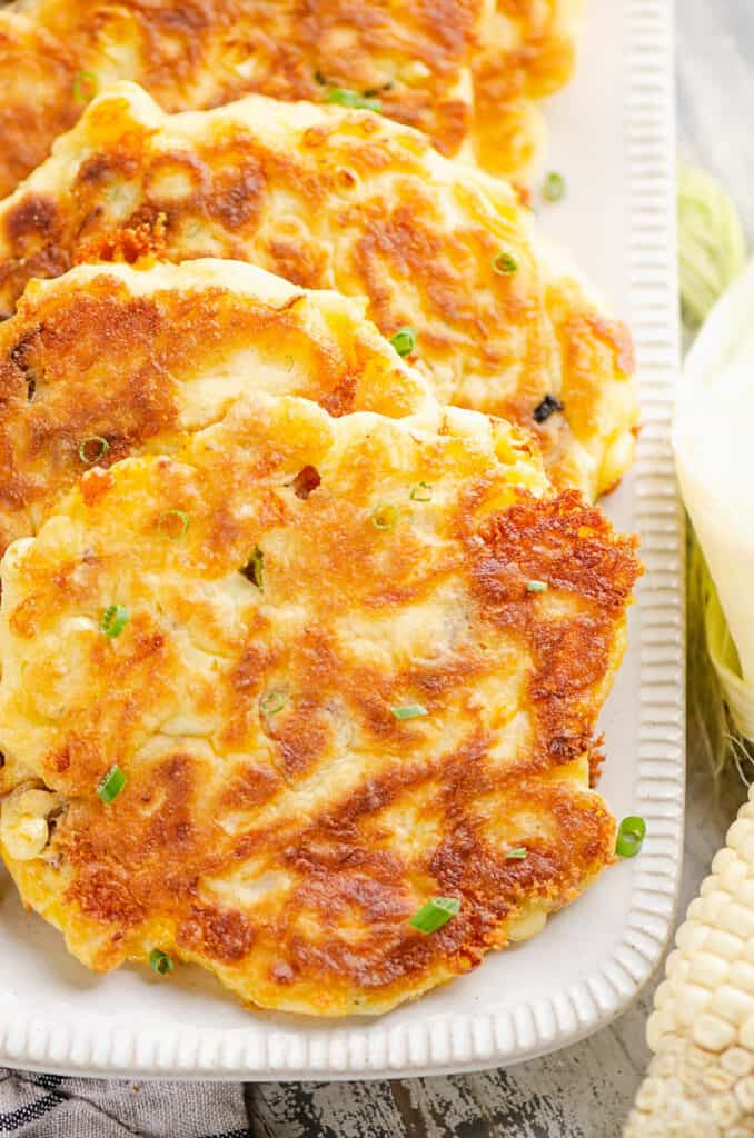 sweet corn fritters topped with chives on platter