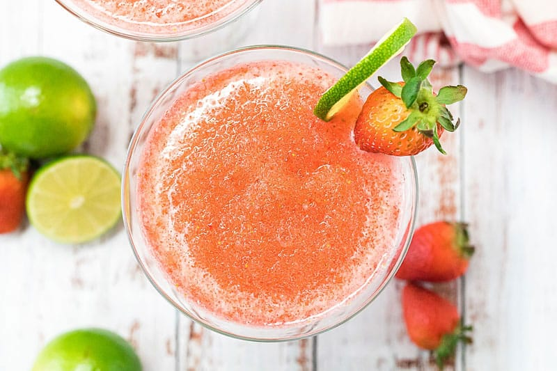 frozen strawberry daiquiri on glass with lime wedge