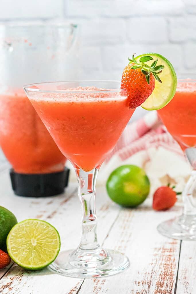 frozen strawberry daiquiri in glass by pitcher