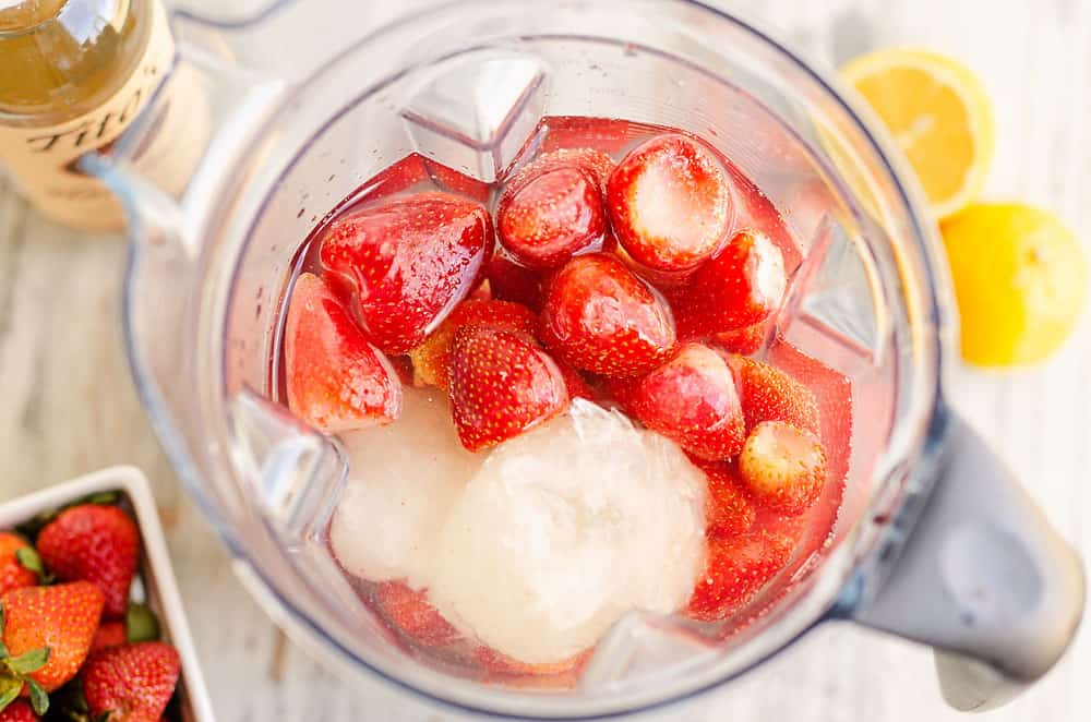 blender filled with lemonade concentrate and strawberries