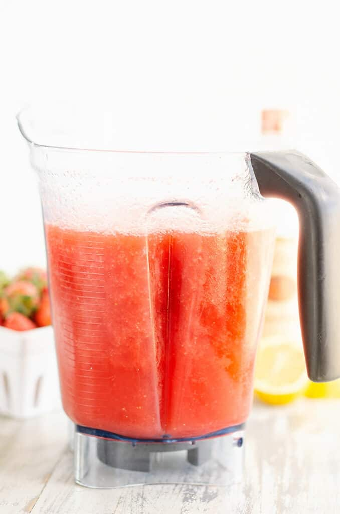 blender filled with frozen blended lemonade concentrate and strawberries
