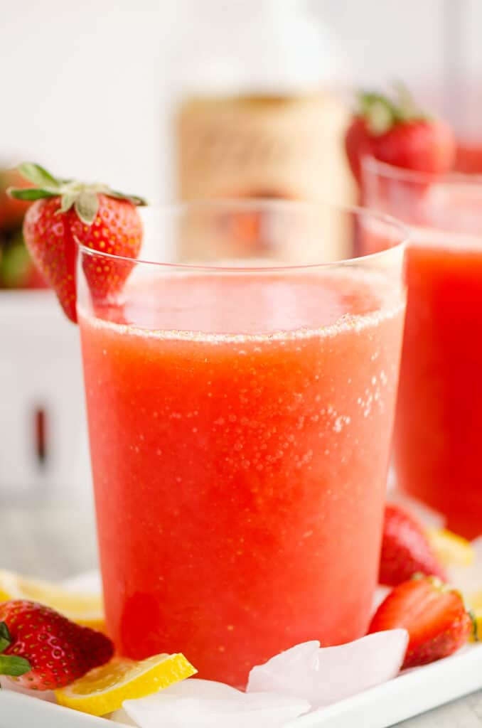 glass of frozen strawberry vodka lemonade topped with strawberry
