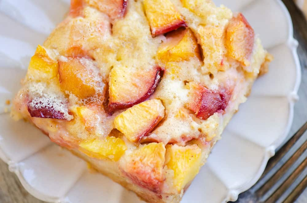slice of peach custard dessert on scalloped plate