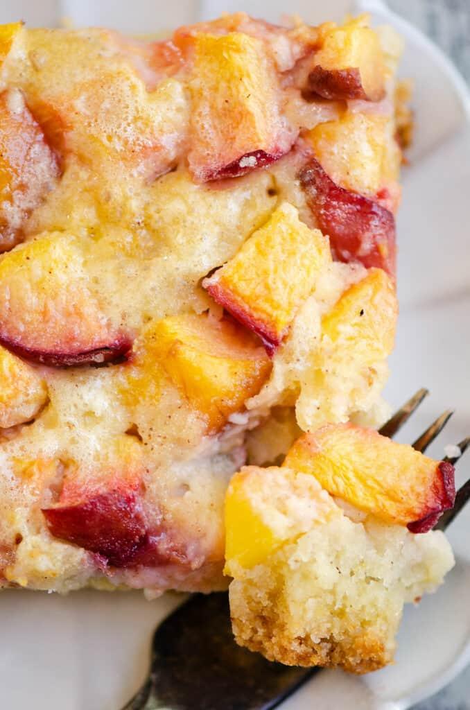 slice of peach custard dessert on plate with fork